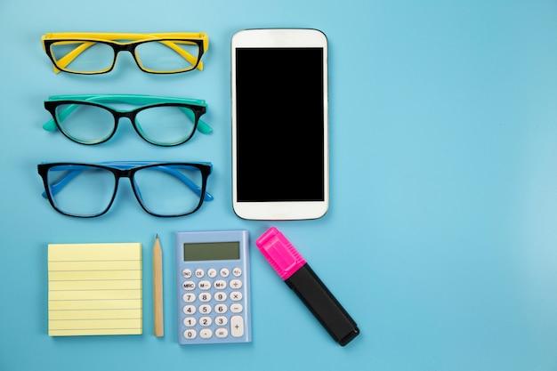 Calcolatore giallo del telefono cellulare del taccuino tre vetri ed indicatore di hilight su stile pastello del fondo blu con il percorso di ritaglio del flatlay del copyspace sul moblie dello schermo
