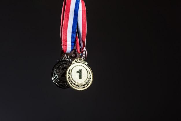 Tre medaglie d'oro, d'argento e di bronzo appese su uno sfondo scuro. sport e concetto di vittoria.