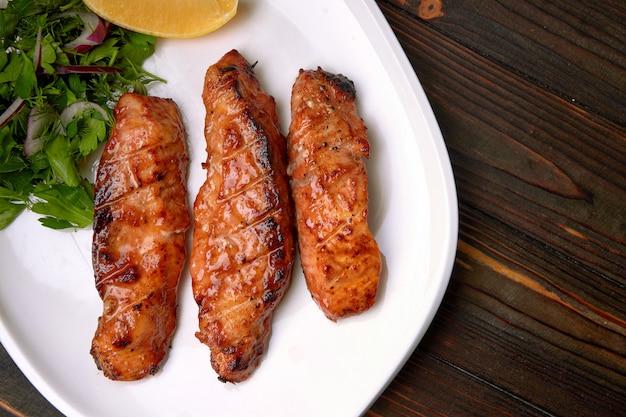 Tre pezzi di filetto di salmone alla griglia, trota, con erbe e limone, su un piatto bianco, su un tavolo di legno