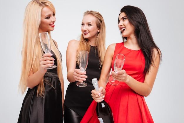 Tre giovani donne attraenti felici con bicchieri e bottiglia di champagne in piedi su sfondo bianco