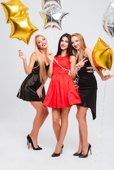 Tre belle giovani donne felici in piedi e in possesso di palloncini a forma di stella su sfondo bianco