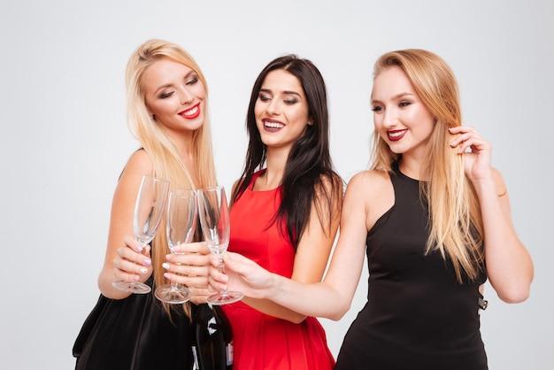 Tre giovani donne affascinanti felici che celebrano e bevono champagne insieme su sfondo bianco