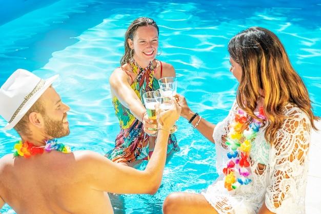 Tre amici felici stanno festeggiando in una piscina