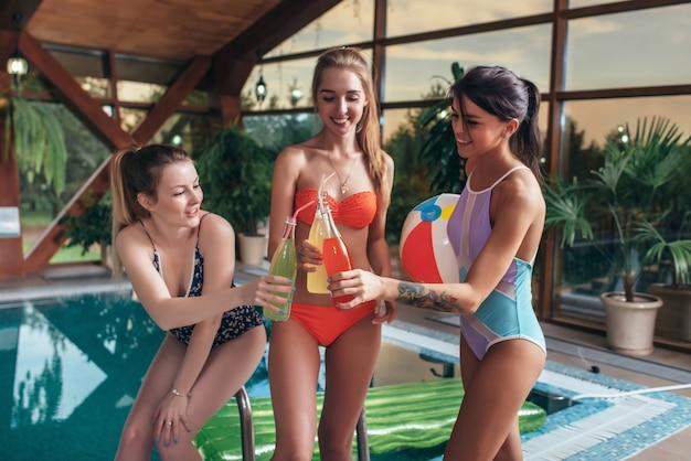 Tre amiche felici in costume da bagno bere succo di bottiglie in piscina nel centro benessere