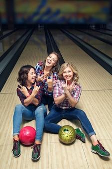 Tre ragazze felici che hanno divertimento seduto sul pavimento nel club di bowling