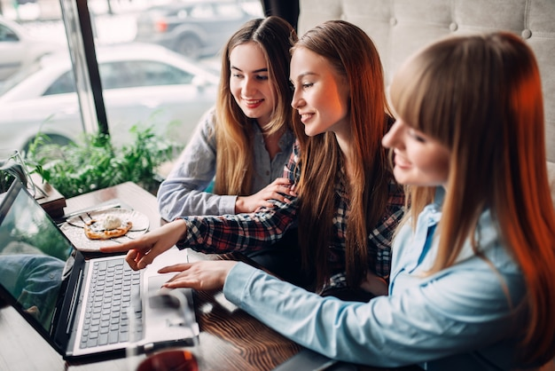 Tre ragazze felici guarda lo schermo del laptop nella caffetteria. dessert al cioccolato e alcol sul tavolo