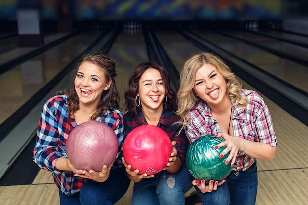 Tre ragazze felici in posa con palle da bowling nel club.