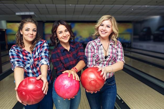 Tre ragazze felici in posa con palle da bowling nel club