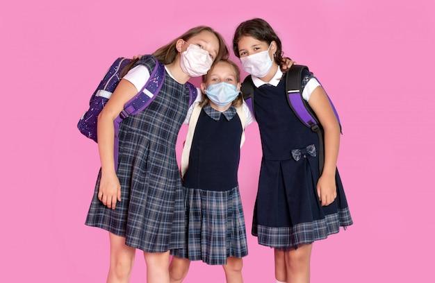 Tre ragazze felici con i capelli lunghi in uniformi scolastiche che indossano maschere mediche