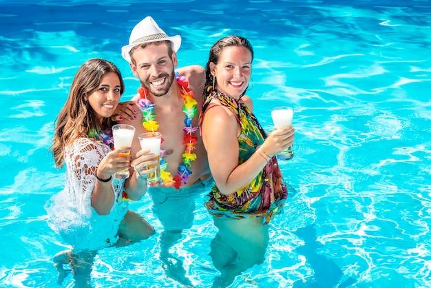 Tre ragazzi felici bevono birra in piscina a una festa