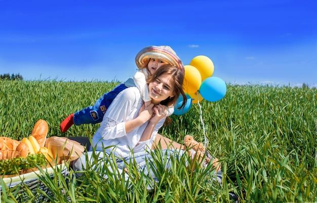 Tre bambini felici che si siedono sul picnic sul campo. cielo blu, erba verde. pane, torte e frutta in un cestino.
