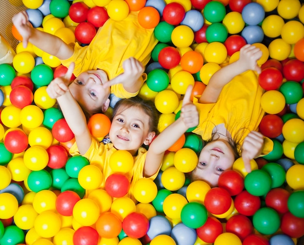 Tre ragazzini felici nella piscina di palline sorridendo