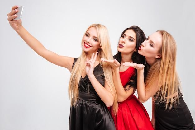 Tre giovani donne allegre felici che inviano baci e si fanno selfie con il telefono cellulare su sfondo bianco