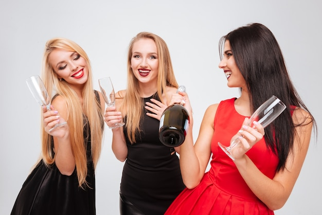 Tre belle giovani donne felici che bevono champagne insieme su sfondo bianco