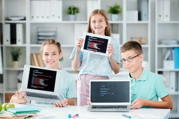 Tre compagni di classe felici e di successo che mostrano le loro presentazioni sui display di gadget mobili dopo averle terminate