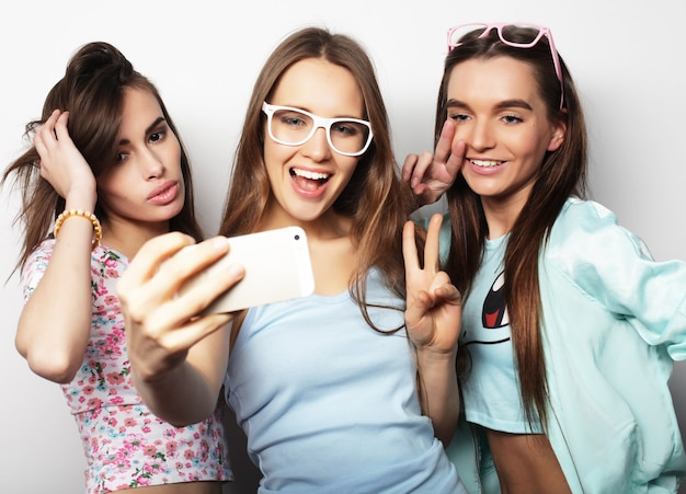 Tre ragazze adolescenti felici dei pantaloni a vita bassa con lo smartphone che prendono selfie