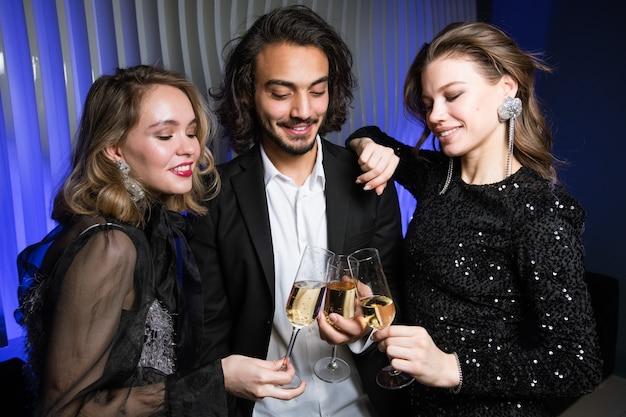Tre amici ben vestiti felici che tostano con flauti di champagne in discoteca mentre si godono la festa