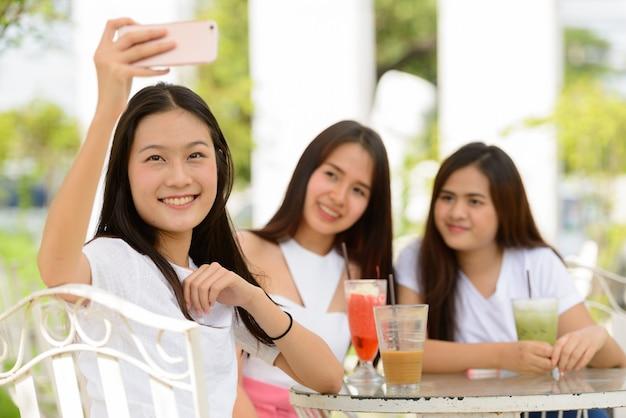 Tre giovani donne asiatiche felici come amici che prendono selfie insieme alla caffetteria all'aperto