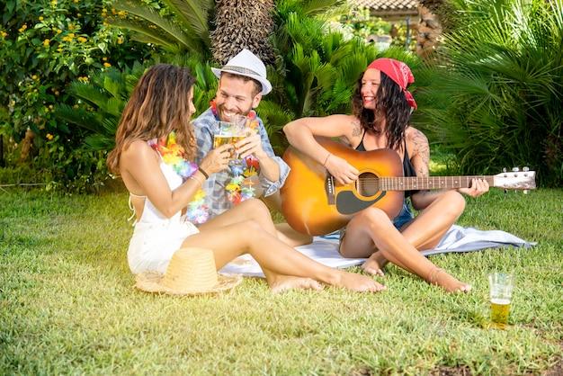 Tre giovani amici donne felici e brindisi maschili con birra a una festa.