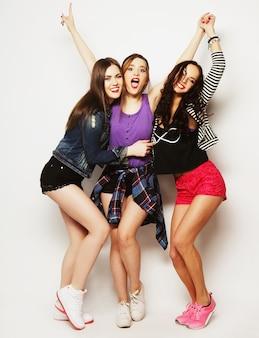 Tre amici di ragazze felici che ballano di gioia in tutta la lunghezza, su sfondo grigio