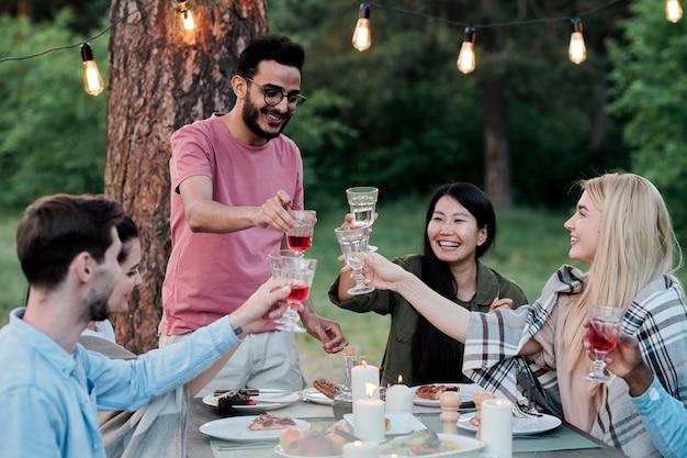 Tre giovani coppie interculturali felici con bicchieri di vino seduti al tavolo servito e brindando per amicizia durante la cena all'aperto
