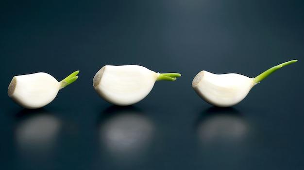 Tre teste d'aglio sono su sfondo blu. verdure fresche e cibo sano