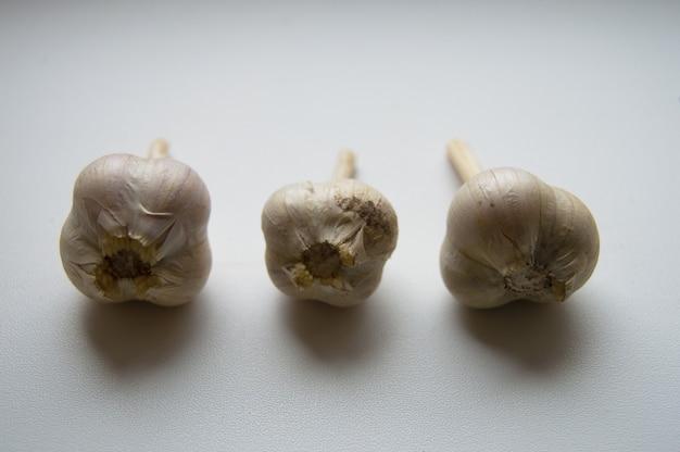 Tre teste d'aglio su sfondo chiaro