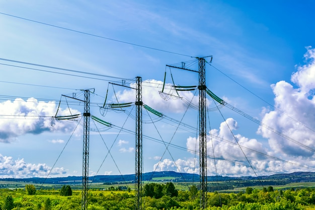 Tre torri di trasmissione ad alta tensione nel cielo nuvoloso