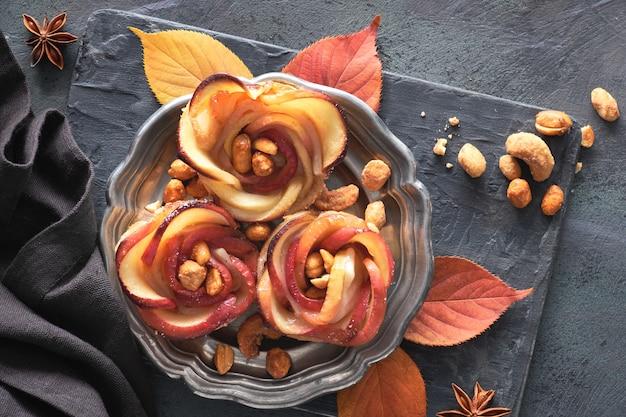 Tre sfogliatine fatte in casa con fette di mela a forma di rosa su piastra metallica, piatto disteso