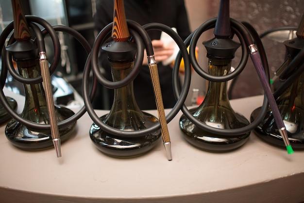 Tre barattoli di vetro del narghilé con il tubo su una tavola nella barra