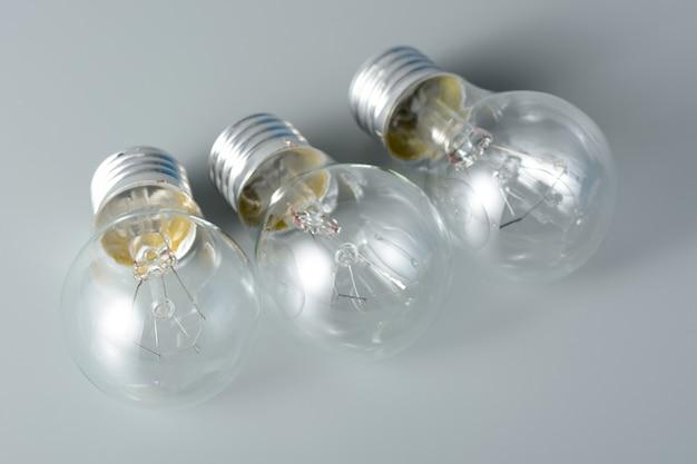 Tre lampadine a incandescenza su sfondo grigio