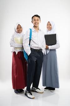Tre adolescenti indonesiani in uniforme scolastica sorridono alla telecamera con uno zaino, un libro e un...