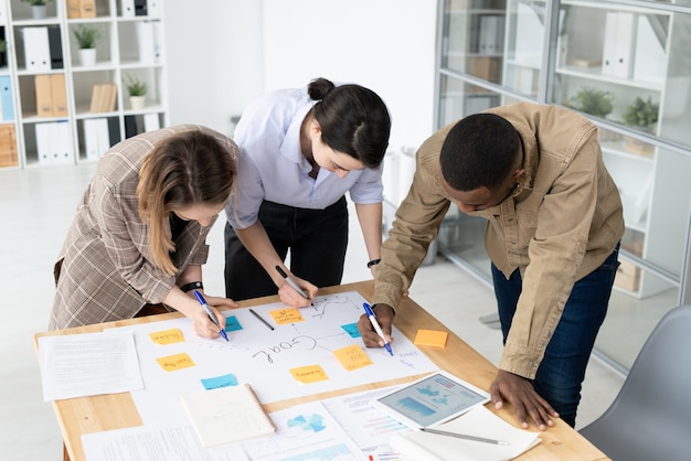 Tre colleghi interculturali con gli evidenziatori chinandosi sul tavolo con fogli e scrivendo idee su fogli di appunti durante il brainstorming