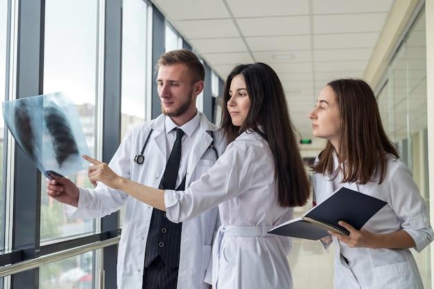 Tre stagisti che esaminano una radiografia dei polmoni per determinare se c'è una polmonite da coronavirus. concetto medico