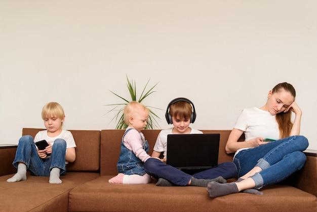 Tre bambini e mamma seduti accanto per usare laptop e telefono. dipendenza da internet.