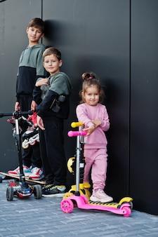 Tre bambini all'aperto contro il muro moderno nero. la famiglia sportiva trascorre il tempo libero all'aperto con scooter e pattini.
