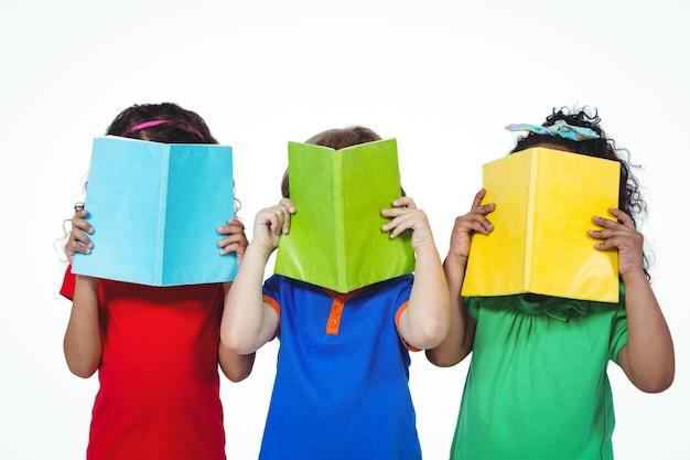 Tre bambini in piedi con i libri davanti ai loro volti