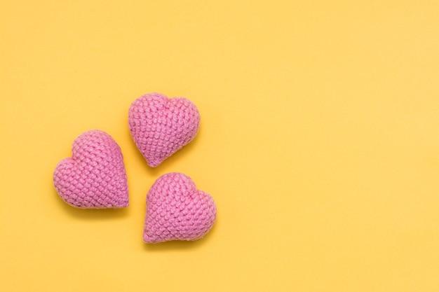 Tre cuori rosa lavorati a maglia su uno sfondo giallo. copia spazio