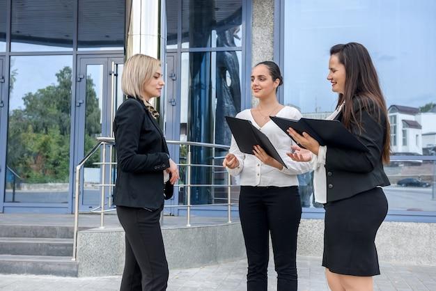 Tre signore in giacca e cravatta in piedi vicino al centro commerciale all'esterno