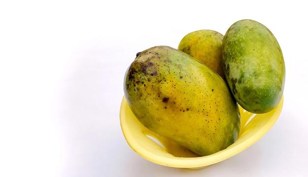 Tre grandi manghi maturi in un cesto isolato su sfondo bianco