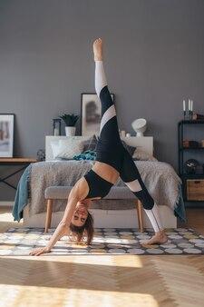 Posa del cane a tre zampe. donna adatta che fa esercizio di yoga di allungamento.