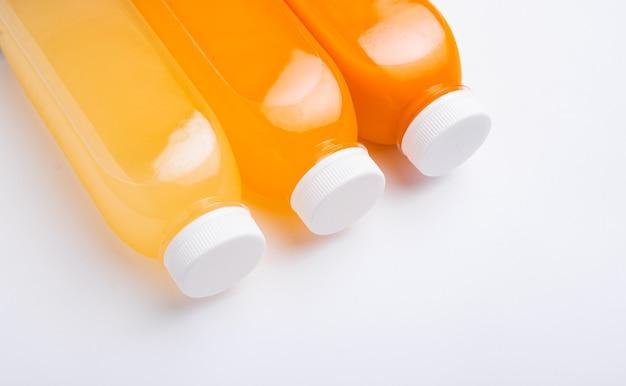 Tre bottiglie di detox di limone, arancia, carota su bianco