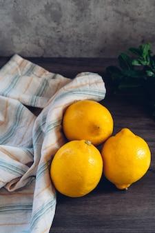 Tre limoni su un tavolo di legno e foglie di menta sullo sfondo