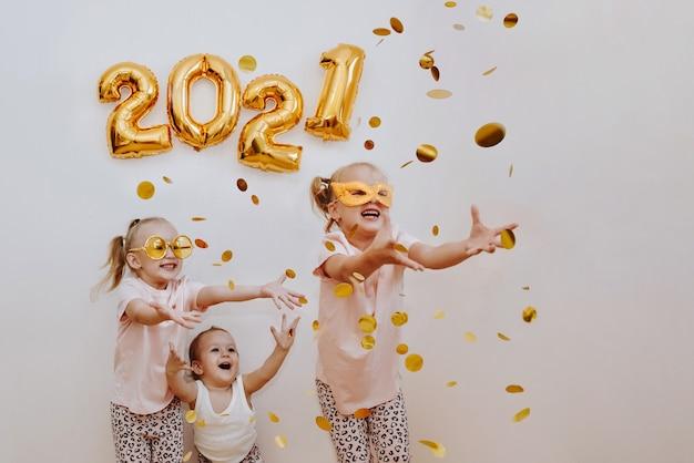 Tre bambine stanno godendo i coriandoli dorati volanti