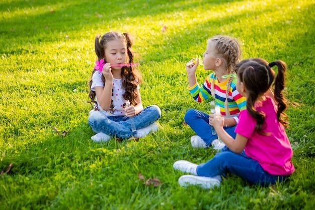 Tre bambine di etnia europea, indiana e asiatica in estate soffiano bolle di sapone giornata internazionale dei bambini