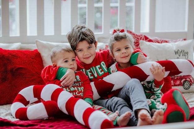 Tre bambini piccoli in pigiama di natale che pone sul grande letto bianco con cuscini di natale.