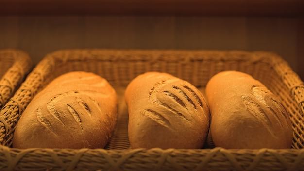 Tre pagnotte di pane di frumento in un cesto. forno