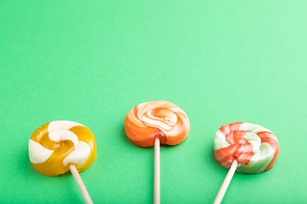 Tre caramelle lecca-lecca su pastello verde