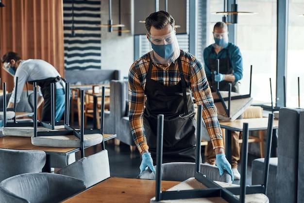Tre camerieri maschi in abiti da lavoro protettivi che sistemano mobili nel ristorante