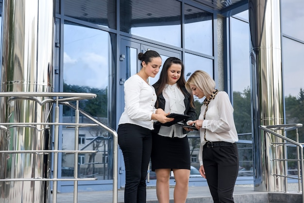 Tre manager con cartelle in posa fuori dall'edificio degli uffici